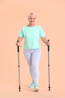 Donna matura con bastoncini da passeggio su sfondo colorato