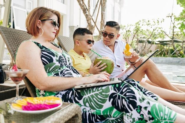 Donna matura che lavora al computer portatile quando suo marito e suo figlio si rilassano sulle sedie a sdraio e bevono cocktail