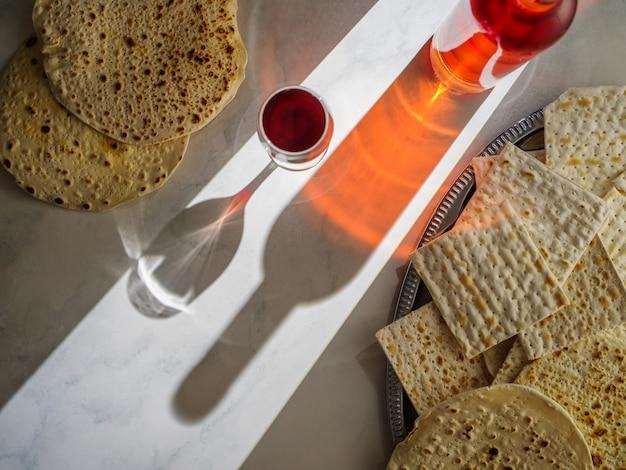 Matzah in un vassoio di metallo, una bottiglia di vino kosher e un bicchiere di vino. vista dall'alto. festa di pasqua.