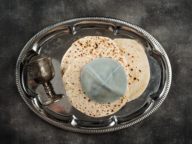 Matzah con una kippah e un bicchiere su un vassoio di metallo. la festa ebraica di pesach.