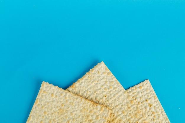 Piatti matzo disposti in qualsiasi forma su una superficie blu