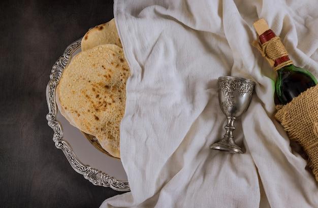 Matzoh festa ebraica rosso kosher bicchieri di vino con una matzah una pasqua haggadah