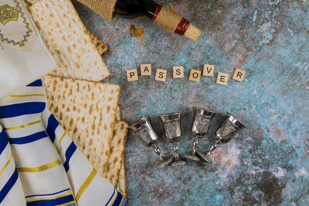 Pane di pasqua ebraica di pane azzimo nella tradizionale vacanza di quattro bicchieri di vino kosher sul tavolo di legno