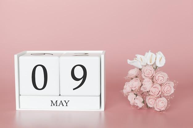 9 maggio. giorno 9 del mese. cubo del calendario sul rosa moderno