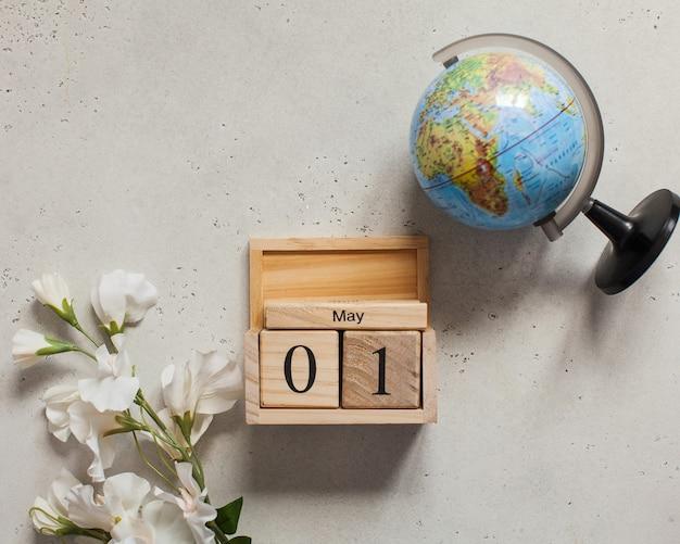 1 maggio su un calendario di legno, accanto a un fiore bianco e un globo