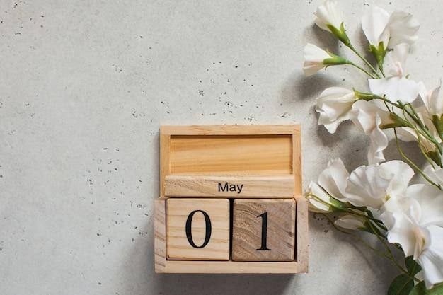1 maggio su un calendario di legno, accanto a un fiore bianco