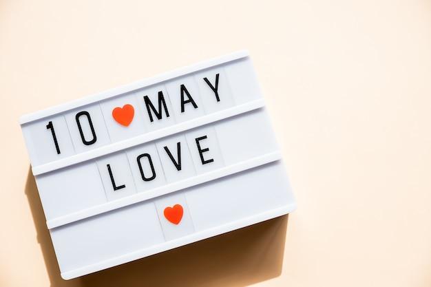 10 maggio festa della mamma carta con piccoli cuori rossi su sfondo pastello. vacanze, cartolina d'auguri. concetto di festa della mamma la migliore mamma di sempre