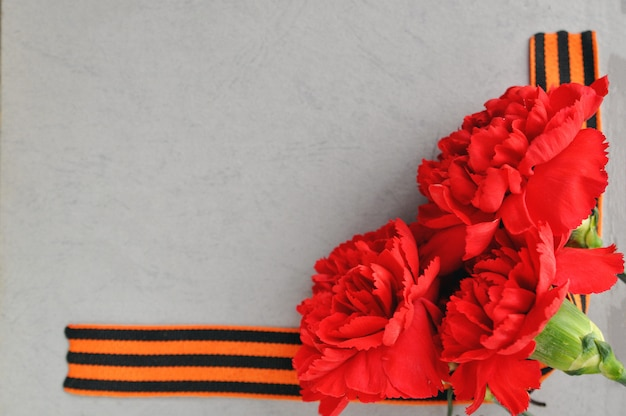 9 maggio carta del giorno della vittoria. garofani rossi e nastro di san giorgio sullo sfondo di un vecchio album di foto.