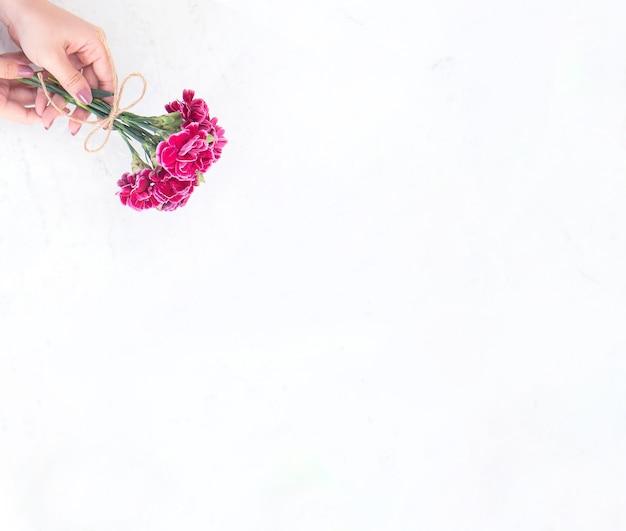 Fotografia di concetto di idea di giorno di madri di maggio - bellissimi garofani in fiore legati da arco di corda che tiene in mano di donna isolato sul tavolo moderno luminoso, spazio di copia, vista piana