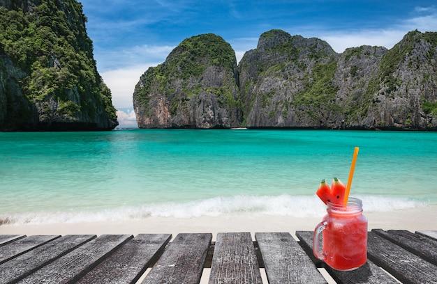 Maya bay island view con tavola di legno e bicchiere di bevanda fredda in illuminazione solare.