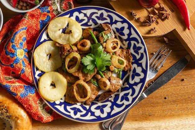 Mazza. piatto caldo uzbeko di fegato di agnello, con l'aggiunta di mele cotte, paprika, aglio, coriandolo, cipolle verdi e salsa di soia.