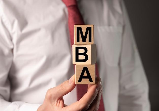 Mba acronimo di laurea magistrale in economia aziendale. concetto di educazione. mani dell'uomo d'affari con i cubi.
