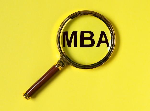 Mba acronimo di laurea magistrale in economia aziendale. concetto di educazione. lente d'ingrandimento per l'apprendimento su superficie gialla.