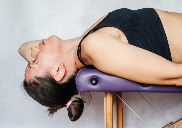 Esercizio del metodo mckenzie per alleviare il dolore al collo, una donna sdraiata sul lettino da massaggio e che abbassa la testa verso il pavimento mentre fa esercizi per alleviare il dolore al collo