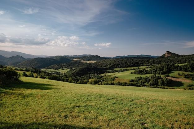 Prati con erba verde, montagne, cielo azzurro con nuvole e paesaggio solare