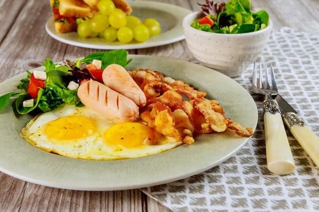 Pasto per colazione uovo, salsiccia, pancetta, insalata con forchetta e coltello