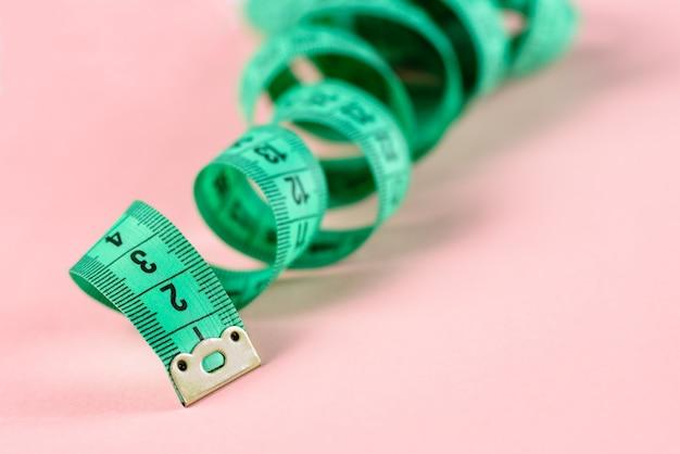 Metro a nastro. tessuto per cucire righello riccio di misurazione del corpo nastro morbido su misura su sfondo rosa rosa.