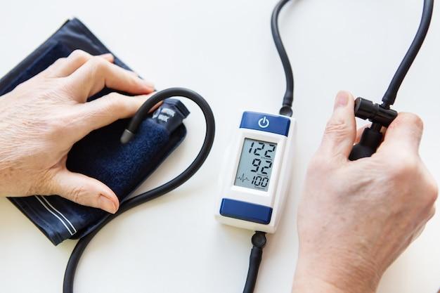 Misurazione della pressione sanguigna. la donna misura la pressione sanguigna. autodiagnosi a casa. vista dall'alto. concetto di salute e cura.