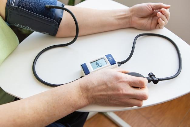 Misurazione della pressione sanguigna. la donna misura la pressione sanguigna. autodiagnosi a casa.
