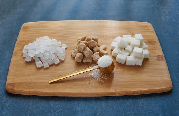 Cucchiaio dosatore con sabbia di zucchero, zucchero in grumi su una tavola di bambù