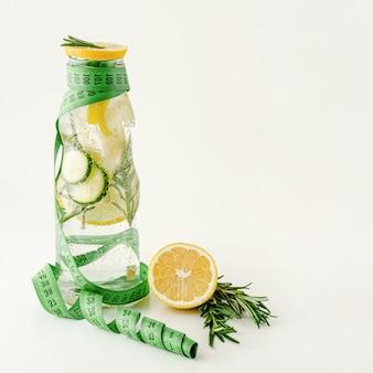 Nastro di misurazione e una bottiglia di acqua disintossicante con limone, cetriolo e rosmarino. perdita di peso e concetto di stile di vita sano