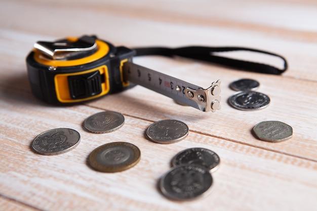 Nastro di misurazione e monete sul tavolo