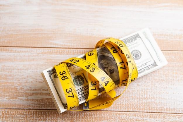 Nastro di misurazione e banconote da un dollaro sul tavolo. ha congelato i soldi
