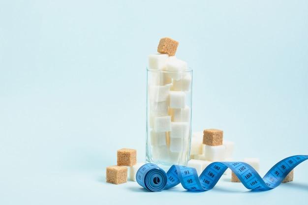 Metro e bicchiere con zollette di zucchero