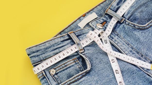 Nastro di misurazione e jeans su uno sfondo giallo brillante. concetto di perdita di peso entro l'estate