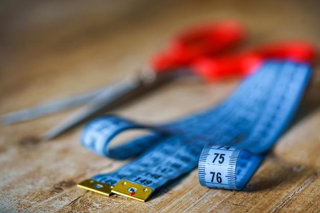 Nastro di misurazione e forbici con manici rossi. il lavoro del sarto. concetto di sarto. avvicinamento.