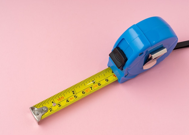Nastro di misurazione con centimetri e pollici su sfondo rosa.