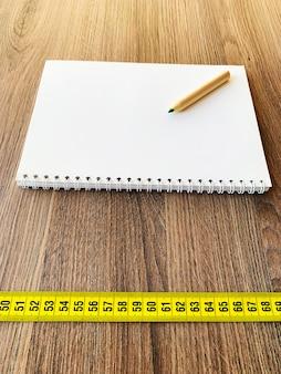 Nastro di misurazione sulla tavola di legno con il blocco note del diario del libro