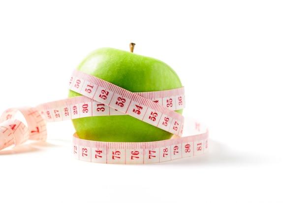 Nastro di misurazione avvolto attorno a una mela verde isolato su sfondo bianco, il concetto dell'obiettivo di perdere peso, l'obiettivo della dieta