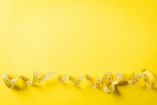 Nastro di misurazione su una parete gialla, simbolo della dieta, concetto di perdita di peso