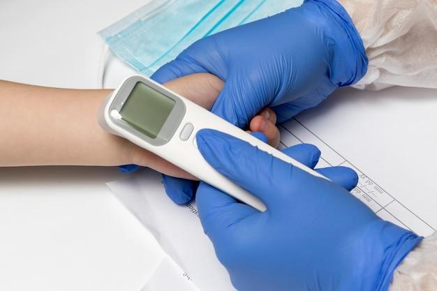 Misurazione della temperatura con un termometro a infrarossi in un bambino. le mani del dottore in guanti da primo piano.