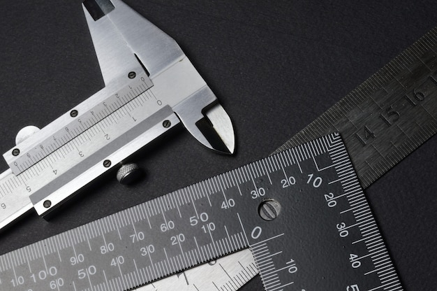Strumento di misurazione, squadra righello e calibro. sdraiarsi su uno sfondo scuro. avvicinamento.