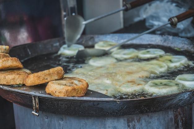 La carne in pastella è fritta in olio sul mercato del cibo di strada in asia phnom penh cambogia