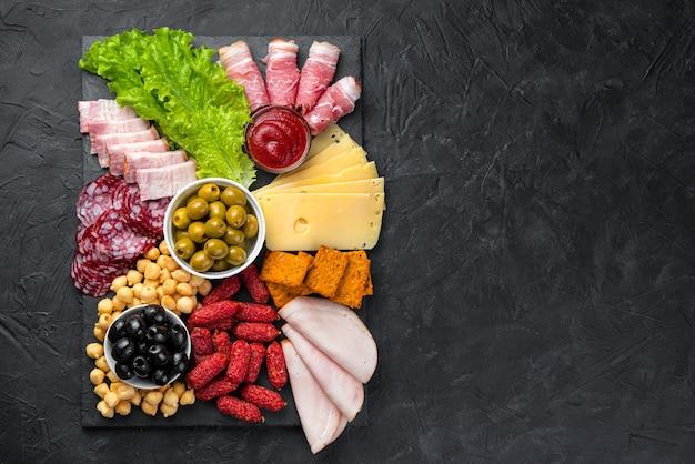 Tagli di carne e formaggio, olive e lattuga. vista dall'alto, copia dello spazio.