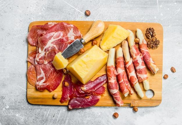 Spuntini di carne e formaggio a bordo sul tavolo rustico.