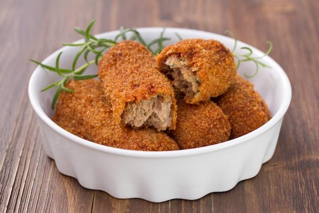 Crocchette di carne in piatto bianco su legno marrone