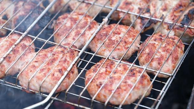 Le cotolette di carne sono grigliate sul primo piano della griglia metallica