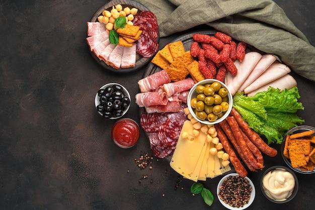 Prelibatezze di carne, tagli di formaggio, salsicce di vario tipo, olive e salse su un tavolo marrone. scrivania culinaria, copia dello spazio.