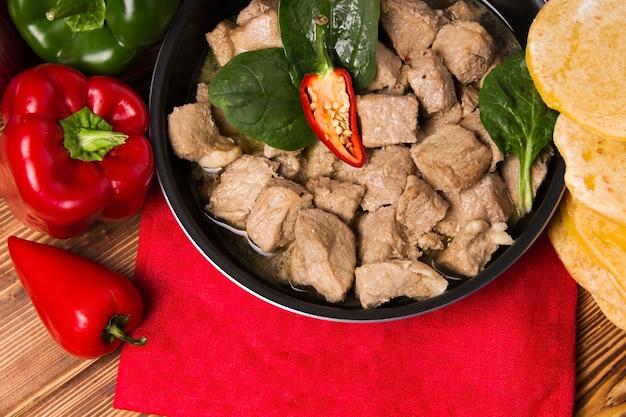Un piatto di carne fritto in padella su tessuto rosso. avere