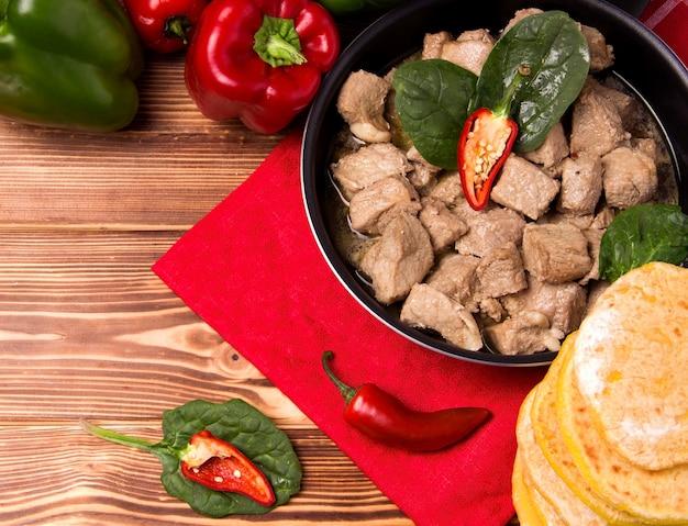 Piatto di carne accanto a verdure in padella su un fondo di legno.