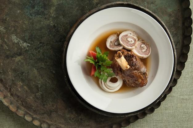 Un piatto di carne con un osso su un vecchio vassoio antico