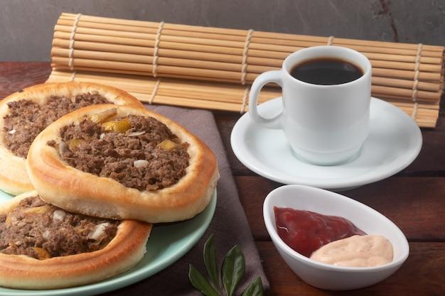 Esfiha di carne con caffè nero.