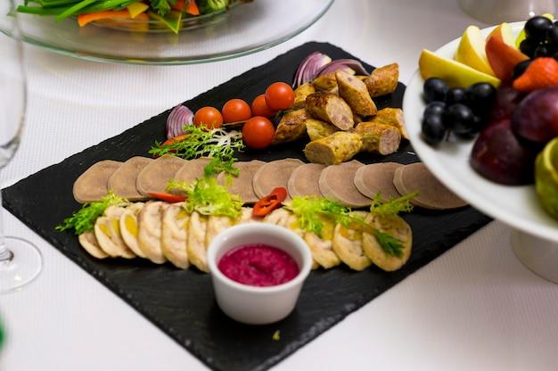Fette di carne e pesce in un ristorante su un tavolo da banchetto e nei piatti