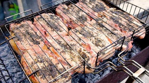 La carne viene cotta alla brace sul fuoco. messa a fuoco selettiva. cibo.