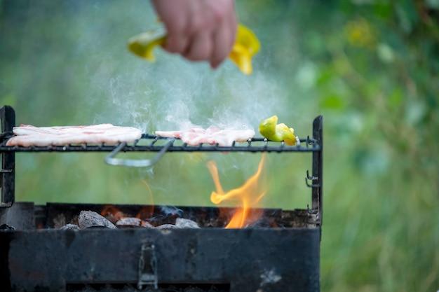La carne viene fritta su una griglia ardente in condizioni di campo