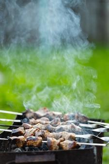 La carne viene fritta su spiedini sul mangal. carne alla brace su spiedini in fumo. kebab alla griglia che cucina in una casa di campagna. copia spazio